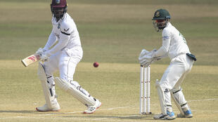 The West Indies' Kyle Mayers (L) plays a shot as Bangladesh's Liton Das looks on during the fifth day of the first cricket Test match between Bangladesh and the West Indies at the Zohur Ahmed Chowdhury Stadium in Chittagong