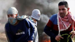 Manifestantes palestinos son vistos durante los enfrentamientos con las tropas israelíes en una protesta contra la decisión del presidente estadounidense Donald Trump de reconocer a Jerusalén como la capital de Israel, cerca de la frontera con Israel al este de la ciudad de Gaza 15 de diciembre de 2017.