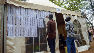 Men in Mali look for their names on a voters list ahead of casting their ballots in the parliamentary elections in Bamako, Mali, 29  March 2020.