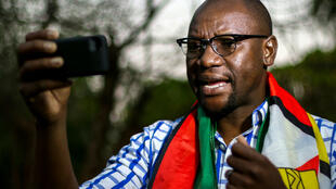 Le pasteur Evan Mawarire, enroulé dans un drapeau du Zimbabwe, en train d'enregistrer une vidéo pour son mouvement anti-Mugabe #TheFlag (LeDrapeau).