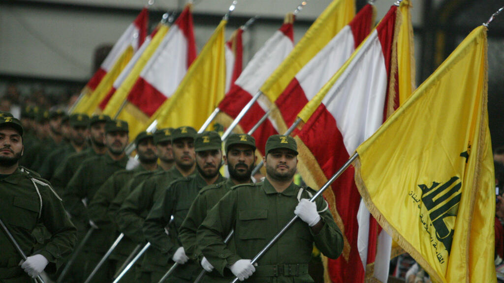 Hezbollah fighters, holding up national flags and the yellow flag of the Lebanese Shiite group, parade on the occasion of Martyr's Day in the southern suburbs of Beirut November 11, 2009.