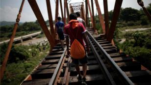 Migrantes, parte de una caravana de miles de personas de América Central camino a Estados Unidos, transitan por las vías del tren, en Arriaga, México, el 26 de octubre de 2018.