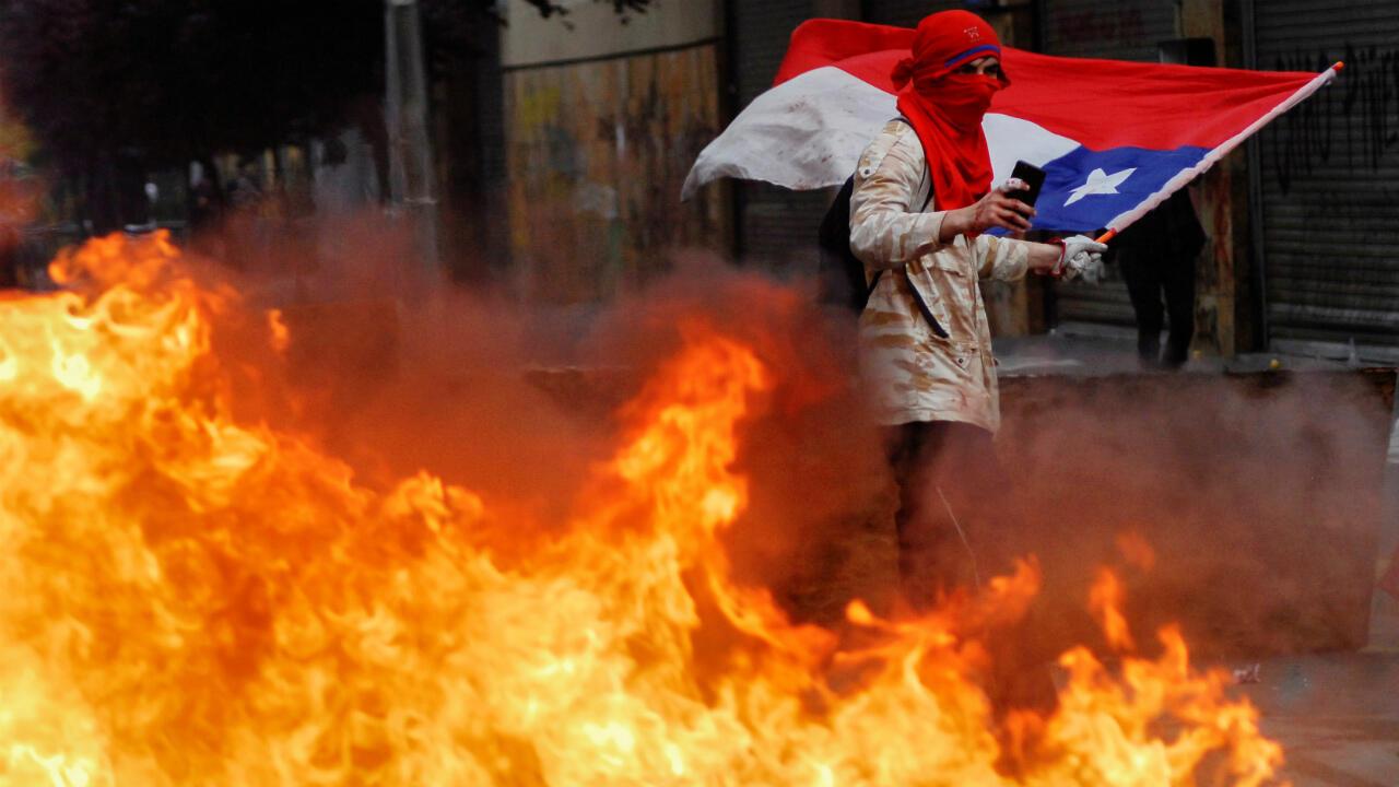 Un manifestant brandit un drapeau national chilien, au milieu des flammes, lors d'une manifestation antigouvernementale à Concepcion, au Chili, le 25octobre2019.