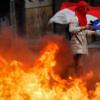 Un manifestant brandit un drapeau national chilien, au miliei des flammes, lors d'un manifestation antigouvernementale à Concepcion, au Chili, le 25 octobre 2019.
