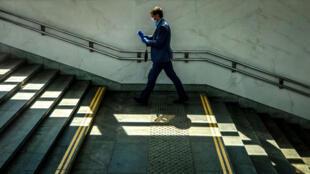 Un hombre con mascarilla y guantes sube unas escaleras en el centro de Moscú el 8 de junio de 2020