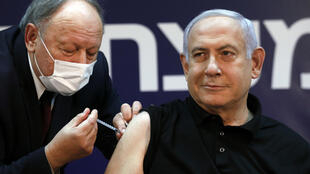 Israeli Prime Minister Benjamin Netanyahu receives a coronavirus jab ahead of the launch of a nationwide vaccination programme on Monday