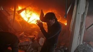 سوري يبحث عن ناجين وسط حريق تسببت به غارة لقوات النظام في دوما في ريف دمشق في السابع من شباط/فبراير 2018