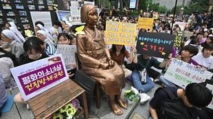 "South Korean protesters sit around a statue of a teenage girl symbolising former ""comfort women"", who served as sex slaves for Japanese soldiers during World War II."