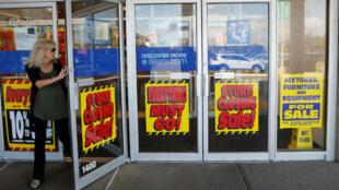 Una mujer sale de un almacén de Sears con letreros de descuentos en New Hyde Park, Nueva York, el 10 de octubre de 2018.