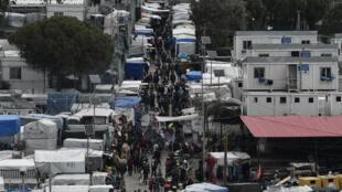 مهاجرون يسيرون في مخيم موريا على جزيرة ليسبوس اليونانية في 5 آذار/مارس 2020