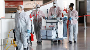 Workers in protective suits get ready to spray disinfectant at Paris Charles de Gaulle airport on May 14, 2020.