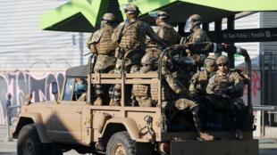 Soldados en un camión militar patrullan las calles en medio de las protestas contra el modelo económico estatal, en Santiago de Chile, Chile, el 21 de octubre de 2019.