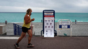 A man wearing a protective face mask runs past a placard by the city of Nice regarding hygienic measures and activities allowed on the beach at the 'Promenade des Anglais' in the French riviera city of Nice, southern France, on May 16, 2020, after France eased lockdown measures taken to curb the spread of the COVID-19 pandemic, caused by the novel coronavirus, on May 11.