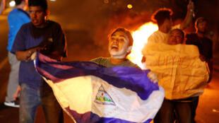 Un manifestante sostiene una bandera de Nicaragua junto a una barricada en llamas mientras los manifestantes protestan por una controvertida reforma a los planes de pensiones del Instituto Nicaragüense de Seguridad Social (INSS) en Managua, el 21 de abril de 2018.