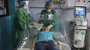 Personal sanitario muestra con una enfermera cómo atender a un paciente usando una cápsula como protección tanto para el paciente como para el personal médico, fabricado en el Instituto Tecnológico de Costa Rica, en Cartago el 8 de mayo de 2020
