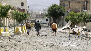 Des habitants de Sanaa marchant dans une rue dévastée par l'explosion d'un dépôt de munitions après un raid de l'aviation saoudienne.