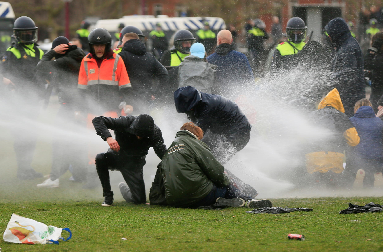 La policía utiliza un cañón de agua durante una protesta contra las restricciones establecidas para frenar la propagación de la enfermedad del coronavirus, en Ámsterdam, Países Bajos, 24 de enero de 2021.