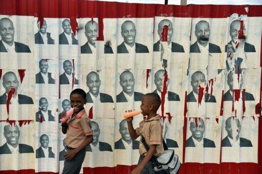 Des écoliers haïtiens passent devant des affiches électorales du candidat à la présidentielle Jovenel Moise, le 21 janvier 2016 à Port-au-Prince