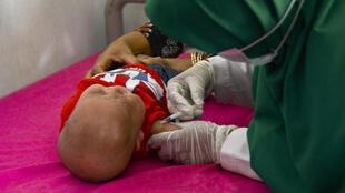 A baby receives the Bacillus Calmette–Guerin (BCG) vaccine for tuberculosis at an integrated services post in Banda Aceh, Indonesia