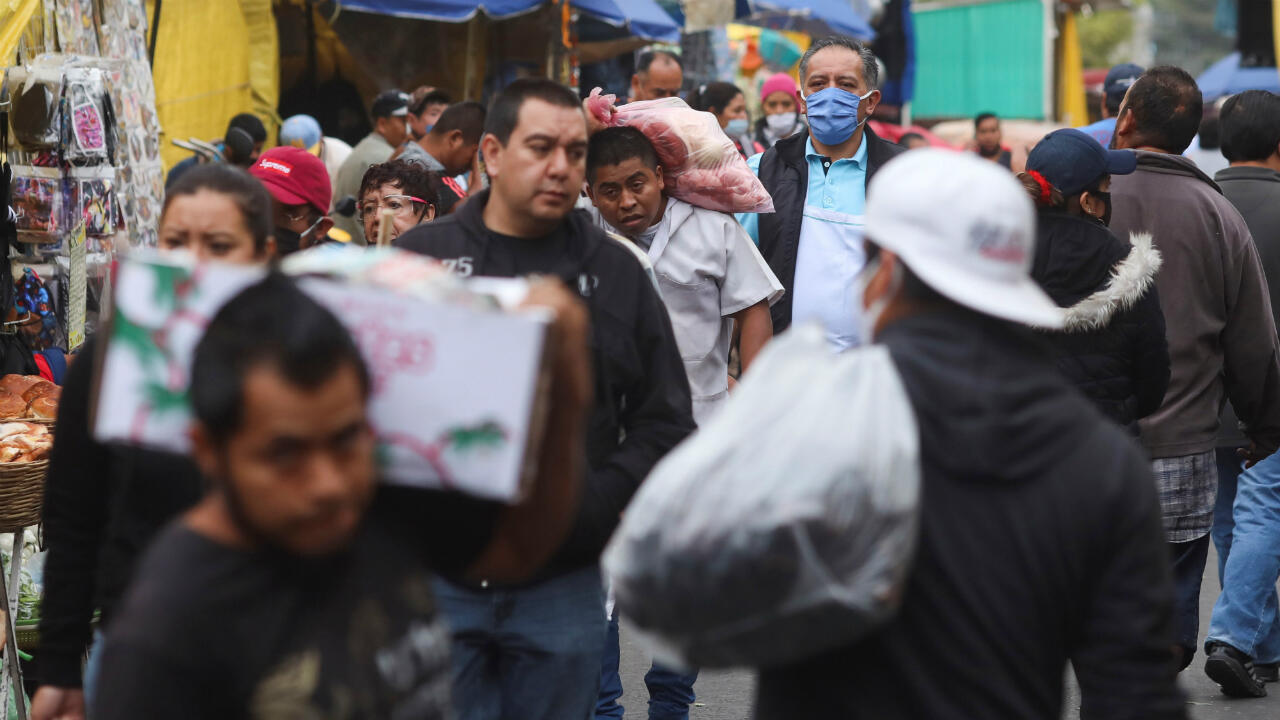 Decenas de personas caminan fuera de un mercado conocido como La Merced, en medio de la reapertura económica en México, a pesar del aumento del brote de Covid-19. En Ciudad de México, México, el 25 de junio de 2020.
