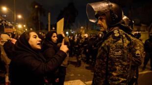 Una mujer que asistía a una vigilia en memoria de las víctimas del Boeing 737 de Ukraine International Airlines, habla con un policía en la capital iraní, Teherán, el 11 de enero de 2020.