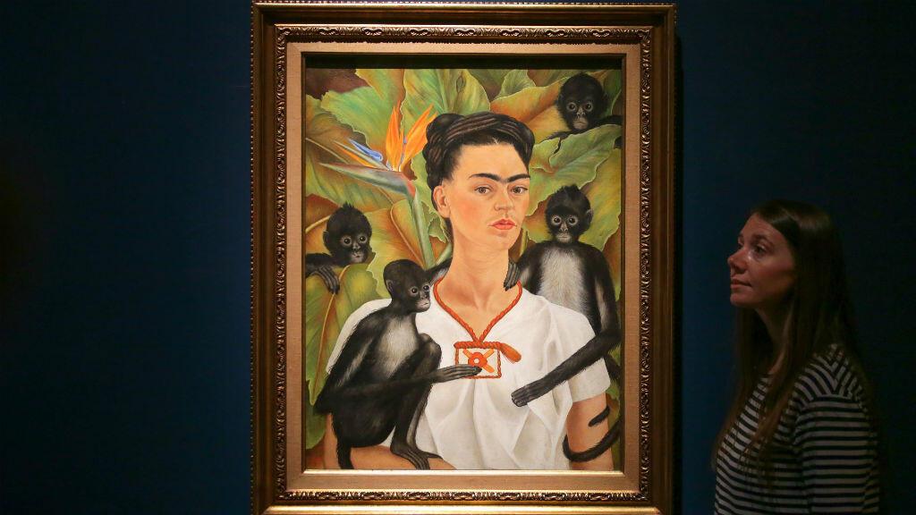Una mujer posa frente a una obra de arte titulada Autorretrato con monos, de Frida Kahlo, 1943, en Coyoacán, México, durante una exhibición en el oeste de Londres, el 13 de junio de 2018.