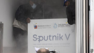Venezuelan airport workers place packages containing 100,000 doses of the Russian Sputnik V vaccine against Covid-19 in a refrigerated truck at the Simon Bolivar international airport in La Guaira, Venezuela on February 13, 2021