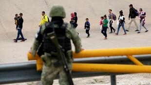 Un soldado de la Guardia Nacional mexicana observa cómo un grupo de inmigrantes atraviesa la frontera de El Paso (Texas) y se dispone a entrar a Estados Unidos.