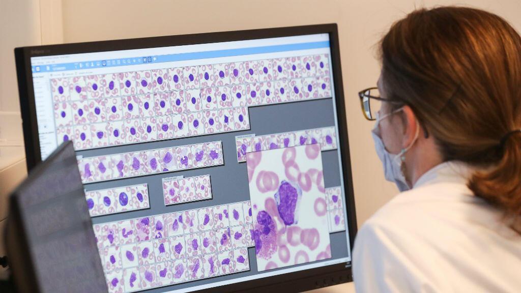 Una investigadora observa un análisis de sangre en el laboratorio de la clínica MontLegia CHC en Lieja, Bélgica, el 26 de marzo de 2020.