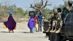 جنود من الجيش النيجيري يمرون أمام أناس يفرون من جماعة بوكو حرام المتطرفة 25 مايو/أيار 2015