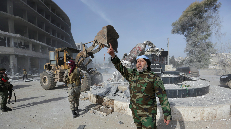 Miembros del Ejército Libre Sirio respaldados por Turquía derrumbando una estatua kurda en el centro de Afrín, Siria, el 18 de marzo de 2018.