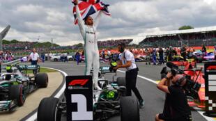 El piloto británico de Mercedes Lewis Hamilton (C) ondea la bandera inglesa mientras celebra en pista después de la victoria en el Gran Premio de Fórmula 1 de Gran Bretaña, en el circuito de carreras de Silverstone, centro de Inglaterra, el 14 de julio de 2019.