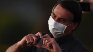 El presidente de Brasil, Jair Bolsonaro, saluda a simpatizantes desde su residencia oficial en Brasilia donde convalece su covid-19, el 20 de julio de 2020