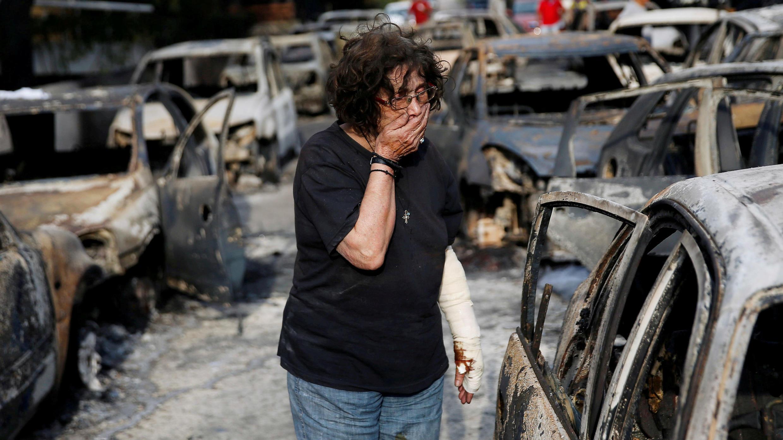 Una mujer reacciona mientras trata de encontrar a su perro, después de un incendio forestal en la aldea de Mati, cerca de Atenas, Grecia , el 24 de julio de 2018.