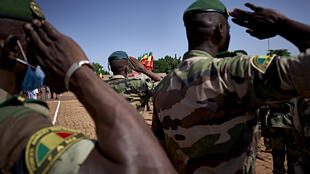 Soldiers of FAMA (Malian Armed Forces) stand and salute during the national anthem at the ceremony of the 60th anniversary of Mali's independence in Bamako, on September 22, 2020.