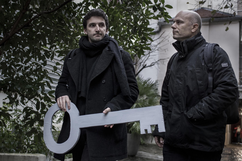 François Graner (à droite) à l'Institut François Mitterand à Paris, portant une clé, symbole de la demande d'accès aux archives du président Mitterrand, le 13 décembre 2017.