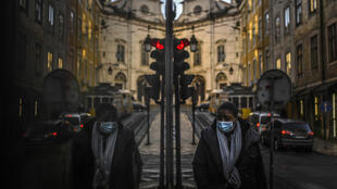 A woman wearing a face mask is reflected in a shop window while walking in Lisbon on January 15, 2021, as Portugal entered a fresh lockdown over a surge in coronavirus cases.
