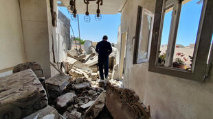 A resident walks through a building damaged by fighting in the Libyan capital Tripoli, on May 1, 2020