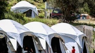 Des agents de sécurité et des membres du personnel médical dans un camp de migrants et de réfugiés, sur l'île grecque de Lesbos, le 13 mai 2020.