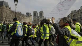 Des manifestants protestent aux abords de la cathédrale Notre-Dame de Paris lors de l'acteXIX des Gilets jaunes, le 23mars2019.