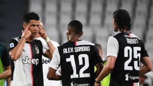 L'attaquant portugais de la Juventus, Christiano Ronaldo, parle à ses joueurs, le défenseur Brésilien Alex Sandro et le milieu de terrain français Adrien Rabiot lors de la victoire en Serie A contre la Lazio Rome le 20 juillet 2020 à Turin