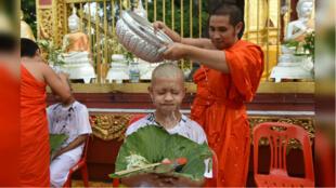 Un monje budista lava la cabeza afeitada de uno de los niños del equipo de fútbol de Tailandia, en medio de una ceremonia religiosa para convertirse en novicios budistas, en un templo de la provincia de Chiang Rai, Tailandia el 24 de julio de 2018.