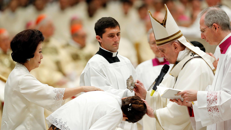 El papa Francisco bautiza a los fieles durante la misa de la Vigilia de Pascua en la Basílica de San Pedro, en el Vaticano, el 20 de abril de 2019.