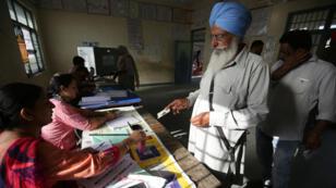 Un ciudadano muestra su identificación en una mesa de votación durante la séptima fase de las elecciones generales en India, en Amritsar, el 19 de mayo de 2019.