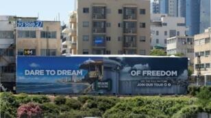 """اللوحة الإعلانية لمنظمة كسر الصمت والتي حولت شعار يوروفيجن """"تجرأ أن تحلم"""" إلى """"تجرأ أن تحلم بالحرية"""" قرب شارع مزدحم في تل أبيب في إسرائيل"""