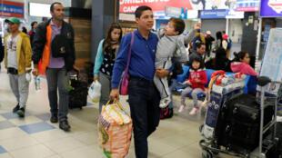 El migrante venezolano Juan Gómez recoge a su familia después de llegar desde Zulia de Venezuela, durante un viaje de cinco días, a la terminal de autobuses de Lima.