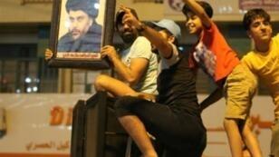عراقيون يحتفلون بنتيجة الانتخابات التشريعية وقد رفع أحدهم صورة الزعيم الشيعي مقتدى الصدر في بغداد