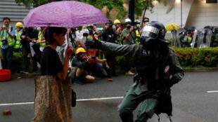 Un policier s'approche d'une manifestante à Tsuen Wan, à Hong Kong, le 25 août 2019.