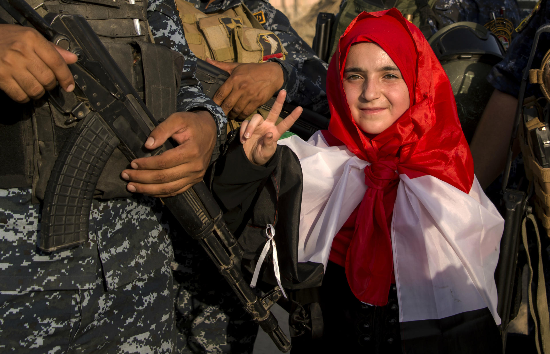 Une petite fille fait le signe de victoire aux côtés des soldats irakiens, le 9 juillet 2017.