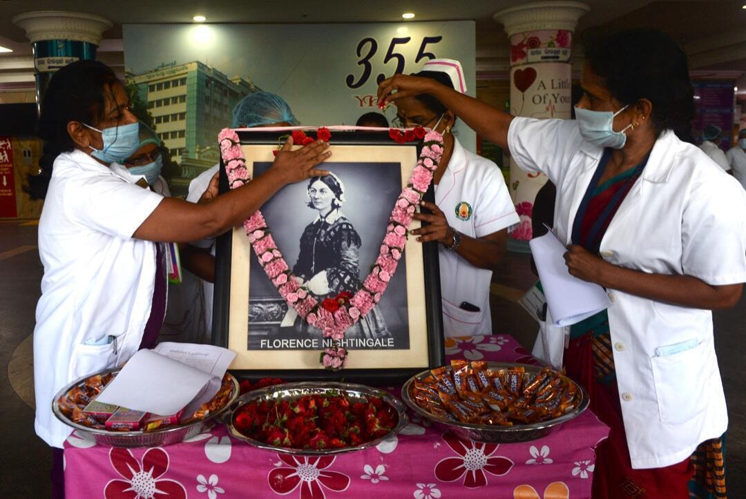 Tres enfermeras decoran una imagen de Florence Nightingale en el hospital Rajiv Gandhi en Chennai el 12 de mayo de 2020, cuando el mundo celebra el Día Internacional de la Enfermería.